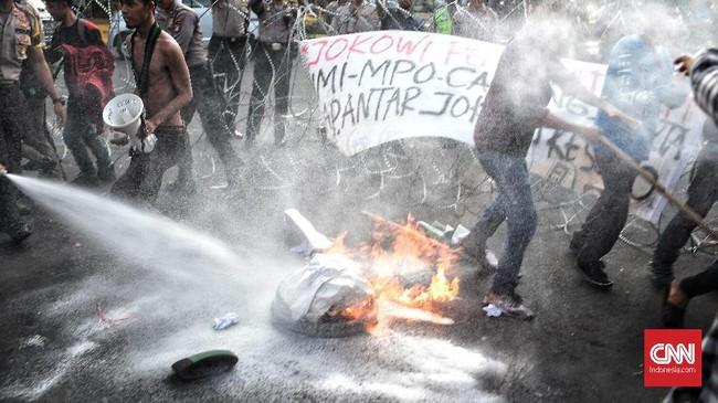 Petugas lalu berbuat sigap dengan berupaya memadamkan api yang membakar ban yang dikobarkan dengan sengaja oleh para mahasiswa pelaku aksi Refleksi 20 tahun Reformasi. (CNN Indonesia/Andry Novelino)