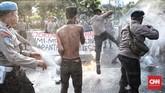 Polisi mencoba membubarkan massa yang tetap melakukan pembakaran ban dalam aksi Refleksi 20 tahun Reformasi di seberang Istana Kepresidenan.(CNN Indonesia/Andry Novelino)