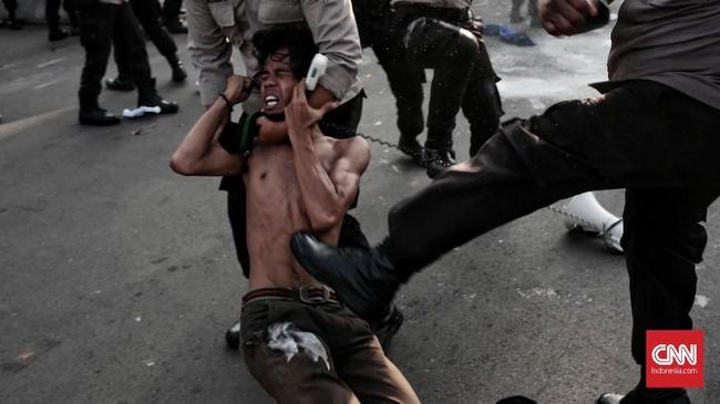 Seorang mahasiswa pelaku aksi mendapatkan aksi pengamanan dari polisi yang menjaga aksi Refleksi 20 tahun Reformasi di depan Istana Kepresidenan, 21 Mei 2018. (CNN Indonesia/Andry Novelino)