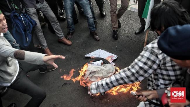 Aksi itu memanas setelah para demonstan membakar ban mendekati ujung kegiatan mereka. Aparat pun bersiaga. (CNN Indonesia/Andry Novelino)