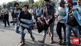 Sejumlah mahasiswa menggotong rekan mereka yang terjatuh di tengah aksi Refleksi 20 tahun Reformasi di seberang Istana Kepresidenan, Jakarta, 21 Mei 2018. (CNN Indonesia/Andry Novelino)
