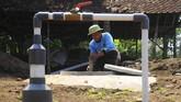 Seorang warga mengontrol endapan kotoran sapi pada digester biogas di Desa Urutsewu, Ampel, Boyolali, Jawa Tengah, Kamis (10/5). Di desa ini, sebagian besar warga beternak sapi, sehingga mereka tak kesulitan mencari bahan dasar berupa kotoran sapi. (ANTARA FOTO/Aloysius Jarot Nugroho)