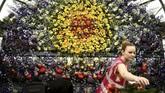 Seorang pekerja terlihat menyusun rangkaian bunga yang dipanjang dengan konsep instalasi beraneka bentuk diRHS Chelsea Flower Show 2018.(REUTERS/Simon Dawson)