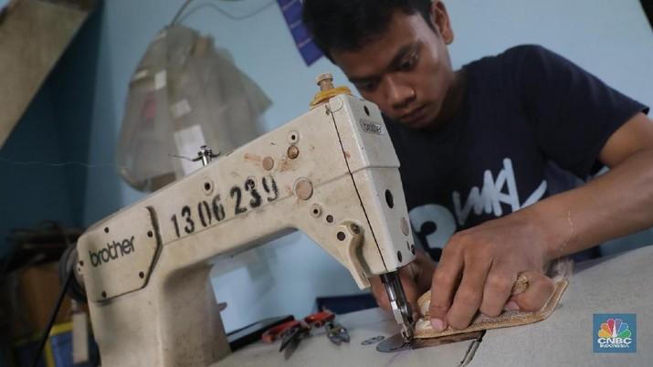 Suasana bengkel atau workshop daur ulang sampah plastik yang terletak di kawasan Pejaten Indah, Pasar Minggu, Jakarta Selatan, Rabu (23/5).  Rumah daur ulang plastik yang telah banyak memproduksi barang-barang cantik dari sisa sampah tersebut. Rumah Workshop ini telah memproduksi banyak barang seperti payung, tas, dompet, dan assesoris lainnya dari produk kemasan plastik yang sudah tidak terpakai seperti produk sabun cuci atau sabun mandi. Salah satu produk tas dompet misalnya, dalam sehari bisa diproduksi mulai dari 4 sampai dengan 7 unit. Rumah daur ulang milik Heriyanti ini sudah lebih dari tujuh tahun berjalan, dan telah memperkerjakan sekitar empat orang. Waktu kerja dimulai dari pagi hingga sore dengan pembagian tugas masing-masing mulai dari persiapan, desain, jahit, sampai pengemasan akhir. Menurut salah satu pekerja di rumah daur ulang itu, saat ini produk yang dibuat lebih banyak tas dengan model selempang. Selain itu ada juga dompet dan payung dengan berbagai ukuran. Untuk harga berkisar antara Rp 50.000 sampai Rp 250.000. Produk yang dibuat biasanya berdasarkan pesanan baik dari domestik maupun ekspor kebeberapa negara di Eropa.  (CNBC Indonesia/Muhammad Sabki)