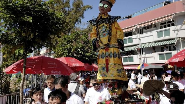 Seorang anak yang mengenakan kostum berdiri di tengah kerumunan orang dalam Bun Festival di Pulau Cheung Chau, Hong Kong, pada Selasa (22/5).