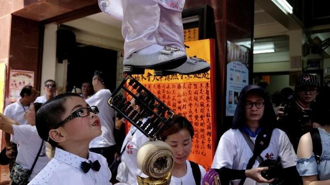 Dalam festival ini anak-anak kecil dipakaikan kostum dan diarak di atas tiang bambu. Merekadiarak di tengah kerumunan pengunjung sambil diiringi barongsai.