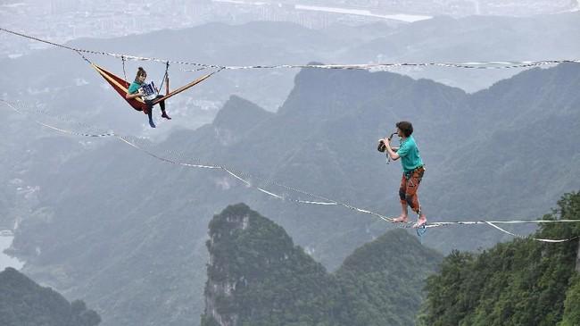 Anggota grup Houle Douce berlatih di atas seutas tali yang menggantung di ketinggian di Taman Nasional Tianmen di Zhangjiajie, Provinsi Hunan, China. (China Daily via REUTERS)