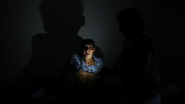 Israel Gonzalez, 84, yang merupakan seorang pasien kanker berpose di bawah cahaya lampu solar di rumahnya di Utuado, Puerto Rico. Terjangan badai Maria delapan bulan lalu membuat nyaris seluruh Puerto Rico kehilangan akses listrik hingga saat ini. (REUTERS/Alvin Baez)
