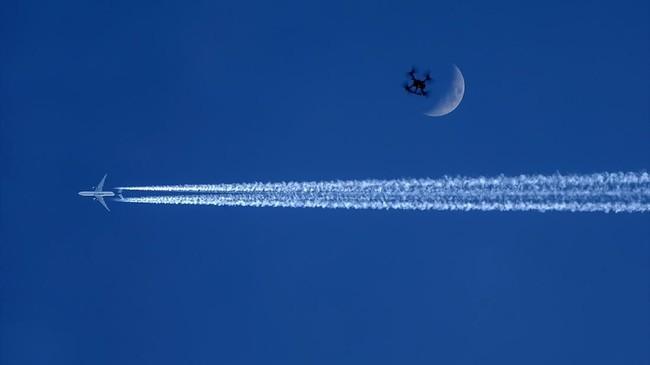Pesawat terbang melewati bulan di atas perbatasan Turki-Irak di distrik Semdinli, kota Hakkari, Turki. (Anadolu)