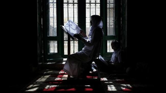 Pria Palestina membaca Alquran di Mesjid Aqsa, Yerusalem, ketika berlangsung bulan Ramadan. (REUTERS/Ammar Awad)
