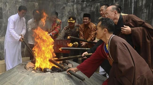 Sejumlah perwakilan umat Budha mengambil Api Dhamma menggunakan obor dari sumber Api Abadi Mrapen, Desa Manggarmas, Godong, Grobogan, Jawa Tengah, Minggu (27/5). Prosesi pengambilan api Dhamma atau api abadi yang kemudian disemayamkan di Candi Mendut. (ANTARA FOTO/Yusuf Nugroho/foc/18)