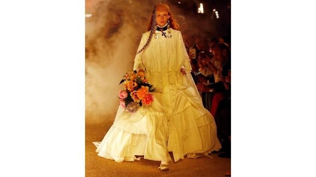 Di antara asap tebal dan kobaran api, menelisik baju yang dikenakan model butuh konsentrasi tersendiri. Michele menghadirkan 114 potongan busana wanita dan pria denganrancangan yang beragam mulai dari bintang rock hingga nuansa abad ke-19. (REUTERS/Jean-Paul Pelissier)