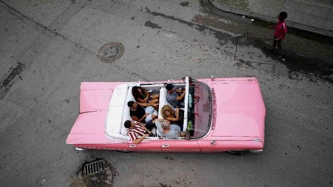 Para wisatawan mengendarai mobil klasik di pusat kota Havana, Kuba. (REUTERS/Alexandre Meneghini)