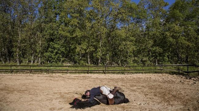 Fernando Noailles berbaring di atas kudanya yang dinamai Madrid. Noailles menggunakan hewan-hewan peliharaannya untuk membantu mereka-mereka yang dilanda kecemasan dan depresi. (REUTERS/Juan Medina)
