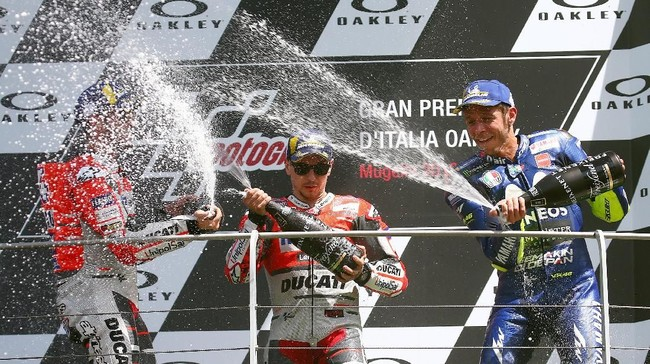 Jorge Lorenzo, Andrea Dovizioso, dan Valentino Rossi menyemprotkan sampanye di atas podium MotoGP Italia 2018. (REUTERS/Alessandro Bianchi)