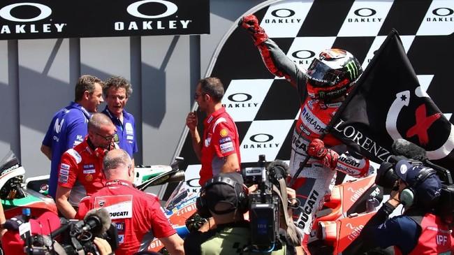 Jorge Lorenzo tiba di parc ferme MotoGP Italia 2018 dan merayakan kemenangan sambil memegang bendera X-Fuera. (REUTERS/Alessandro Bianchi)