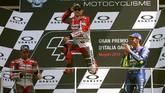 Jorge Lorenzo melompat dari podium untuk merayakan gelar MotoGP Italia 2018 dengan mendapat tepuk tangan dari Valentino Rossi dan Andrea Dovizioso. (REUTERS/Alessandro Bianchi)