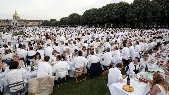 Sejumlah wisatawan dan warga Paris meramaikan gelaran tahunan 'Diner en Blanc' atau makan malam dalam balutan busana serba putih, di Les Invalides, Paris, Perancis, Minggu (3/6). (REUTERS/Benoit Tessier)