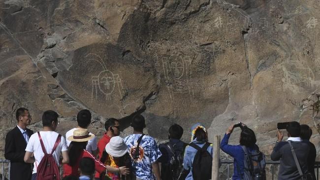Pengunjung mengamati lukisan batu yang terdapat di Gunung Helan.