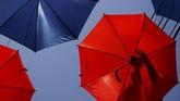 Seorang pekerja mengatur payung-payung berwarna yang menggantung di atas sebuah jalan. Payung itu dipasang dalam rangka persiapan jelang suatu festival musik di Zabbar, Malta. (Reuters/Darrin Zammit Lupi)