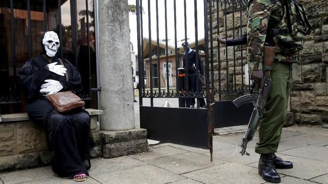 Di luar gedung parlemen di Nairobi, Kenya, seorang polisi berjaga-jaga dekat seorang aktivis lingkungan yang mengenakan kostum. Aktivis itu memprotes rencana pembangunan pabrik batu bara. (Reuters/Baz Ratner)