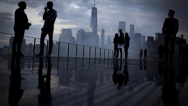 Garis langit kota Manhattan terlihat ketika orang-orang berkumpul di runway di peragaan busana pria koleksi musim semi dan musim panas Saint Laurent 2019 di taman patung Liberty di New Jersey, Amerika Serikat. (Reuters/Andrew Kelly)