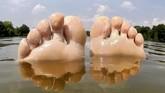 Jari-jari kaki seorang wanita yang sedang mengambang di danau Irensee di Uetze, dekat Hanover, Jerman bagian utara. (AFP/dpa/Hauke-Christian Dittrich)