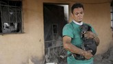 Walter Amilcar Garcia, misalnya, baru saja menyelamatkan anjing peliharaan abangnya di depan rumah di Escuintla yang hancur akibat erupsi Gunung Fuego. (Reuters/Carlos Jasso)