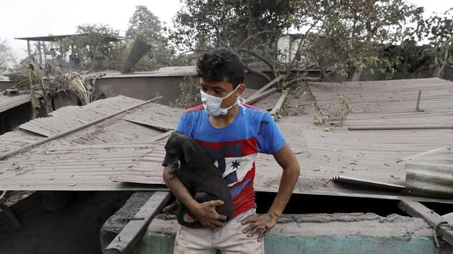 Sementara itu, Jonathan Castellanos hanya bisa meratapi rumahnya yang hancur, tapi ia bersyukur masih bisa menyelamatkan anjing peliharaannya. (Reuters/Carlos Jasso)
