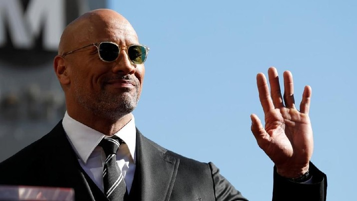 Actor Dwayne Johnson waves before unveiling his star on the Hollywood Walk of Fame in Los Angeles, California, U.S., December 13, 2017. REUTERS/Mario Anzuoni