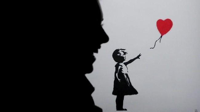 Bayangan seorang perempuan yang tertawa sementara karya seni Banksy yang ditampilkan di Moskow, Rusia, terlihat di belakang. (Reuters/Maxim Shemetov)