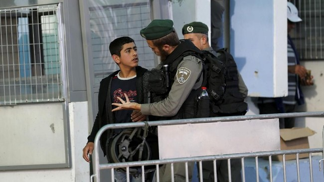 Di bawah penjagaan ketat, mereka khusyuk berdoa. (Reuters/Mussa Qawasma)