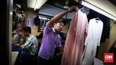 Sejumlah jasa penjahit sibuk menyelesaikan pesanan di kios Pasar Atom, Pasar Baru Jakarta. Saat mendekati hari raya Idul Fitri, penjahit yang ada di sana disibukan dengan pesanan dari warga, mulai jahitan, obras, hingga pemotongan pakaian. (CNNIndonesia/Safir Makki)
