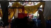 Seorang pria beristirahat sembari memainkan ponselnya di penampungan sementara pengungsi Gunung Fuego, di Escuintla, Guatemala, Jumat (8/6). (REUTERS/Carlos Jasso)