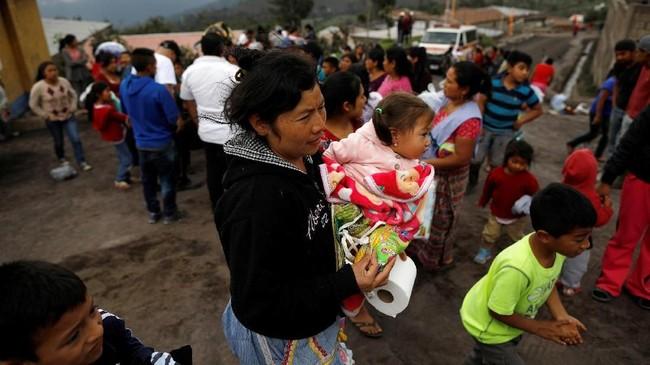Seorang warga yang terdampak letusan Gunung Fuego membawabarang-barang kebutuhan sehari-hari yangdidapat daripetugas sambil menggendong bayi, di desa Sangre de Cristo, Chimaltenango, Guatemala, Kamis (7/6). (REUTERS/Jose Cabezas)