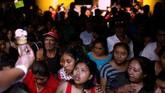 Para pengungsi berkerumun menanti es krim dari petugas, di tempat perlindungan sementara, di Escuintla, Guatemala, Kamis (7/6). (REUTERS/Carlos Jasso)