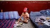 Seorang anak memakaitopeng Spiderman sambil menyantap makanannya, di tempat pengungsian di sebuah sekolah, di Escuintla, Guatemala, Rabu (6/6). (REUTERS/Carlos Jasso)