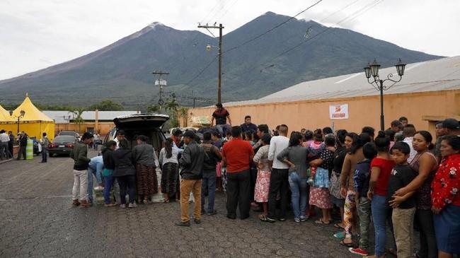 Pengungsi mengantri bantuan dari petugas pasca-erupsi Gunung Fuego, di Alotenango, Guatemala,Jumat (8/6). (REUTERS/Jose Cabezas)