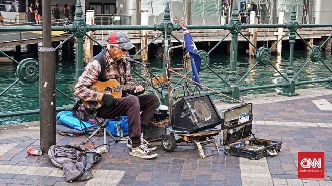Musisi jalanan masih bisa dijumpai saat wisatawan berkeliling di kawasan Kota Sydney. Salah satunya seorang pria paruh baya yang memainkan gitar kecil dan harmonika di kawasan Circular Quay.