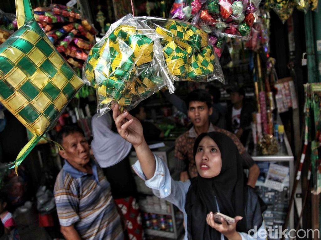 Seorang warga tengah memilih ketupat plastik.