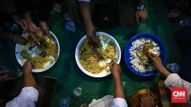 Nasi kebuli disantap bersamaan dengan lauk potongan kambing dan juga ayam ditambah acar. Budaya arab sangat kental sekali khususnya kuliner saat buka puasa bersama di Masjid Azzawiyah Pekojan Jakarta. (CNNIndonesia/Safir Makki)