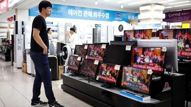 Seolah tak membiarkan seorang pun ketinggalan kabar besar ini, toko elektronik di Korea Selatan turut menayangkan beritanya di etalase televisi yang dijual. (REUTERS/Kim Hong-Ji)