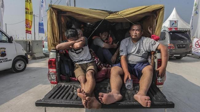 Pemudik berada di dalam angkutan bak terbuka di Jalur Tol Pejagan-Pemalang, Tegal, Jawa Tengah, Minggu (10/6). Meski pihak kepolisian melarang penggunaaan kendaraan bak terbuka untuk mudik, tapi masih banyak pemudik yang melakukan hal tersebut. ANTARA FOTO/Muhammad Adimaja/kye/18