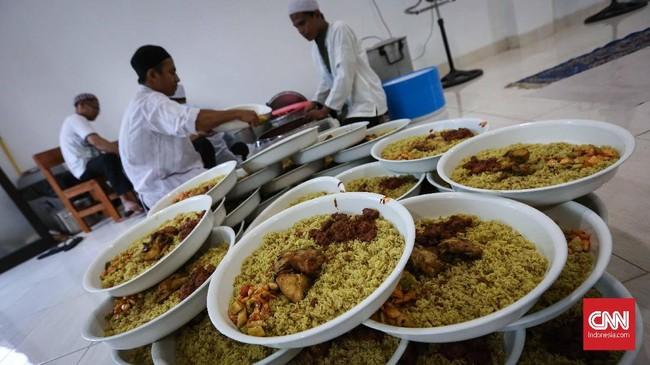 Para jamaah menyiapkan nasi kebuli yang akan disantap bersamaan saat buka puasa di Masjid Azzawiyah, Pekojan Jakarta. Tradisi turun temurun ini selalu dilakukan di malam 27 Ramadan bertepatan dengan khataman Al quran. (CNNIndonesia/Safir Makki)