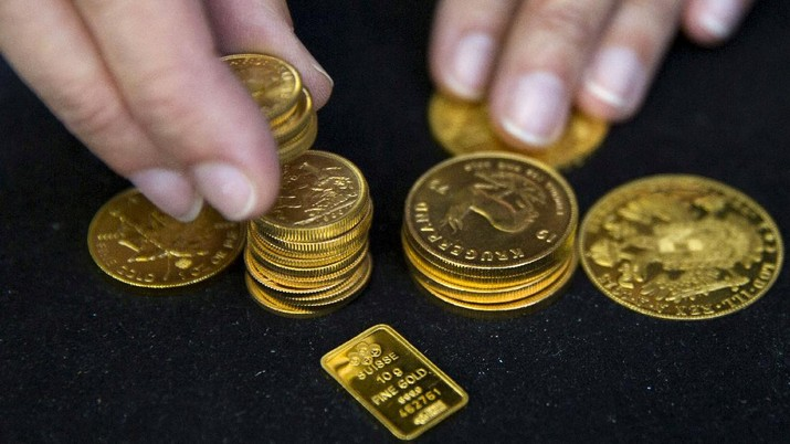 FILE PHOTO: A worker places gold coins on display at Hatton Garden Metals precious metal dealers in London, Britain July 21, 2015. REUTERS/Neil Hall/File Photo