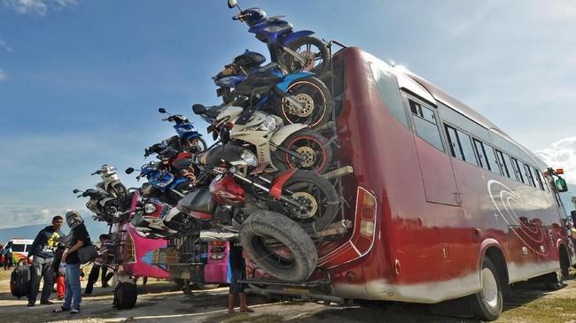 Membawa sepeda motor menuju kampung halaman menjadi pilihan sebagian pemudik guna menghemat pengeluaran, tenaga dan waktu. Tidak adanya angkutan khusus sepeda motor terutama saat musim mudik, membuat motor-motor pemudik diangkut dengan bus. (ANTARA FOTO/kye/18)