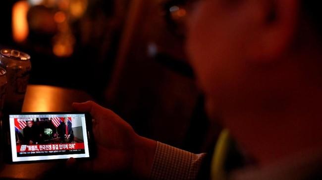 Jika koran dianggap sudah terlalu kuno, pertemuan bersejarah itu bisa disaksikan secara langsung lewat gawai dengan mengakses situs-situs berita terkemuka.(REUTERS/Andrew Kelly)