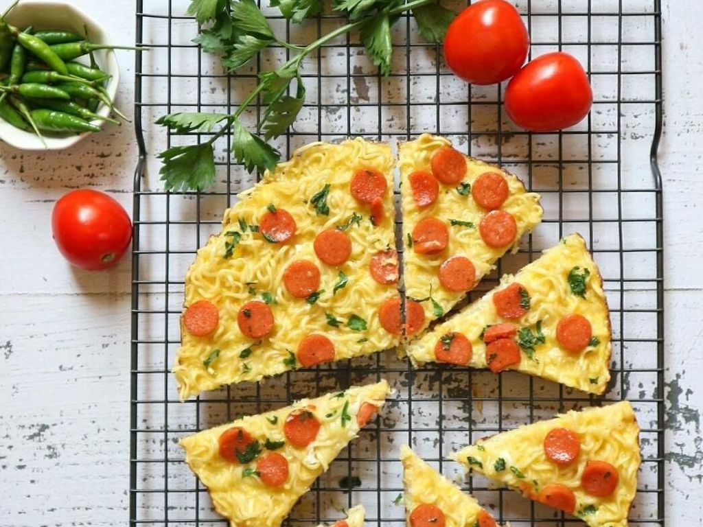 Omelet mie buatan akun @dhora_kusumadewi ini sengaja diberi topping irisan sosis. Sepintas omelet mie ini terlihat seperti satu pan pizza, ya. Foto: Instagram