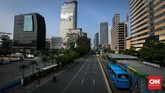 Jalan MH Thamrin yang menjadi jantung kota Jakarta juga hanya dilintasi kendaraan pribadi. Angkutan umum seperti bus dan transjakarta masih beroperasi melayani segelintir penumpang. (CNNIndonesia/Safir Makki)