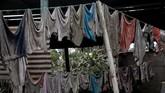 Pakaian yang menggantung dan tertutup abu menunjukkan betapa penduduk kota tak bersiap sama sekali menghadapi gunung berapi tersebut. Banyak dari mereka yang bahkan masih menyantap makan siang sebelum abu panas menyerang pada sore hari. (REUTERS/Carlos Jasso)
